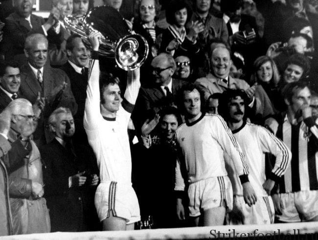 Франц Беккенбауэр держит над головой Кубок европейских чемпионов, в то время как его товарищи по команде Джонни Хансен и Герд Мюллер наблюдают за реакцией фанатов «Баварии»