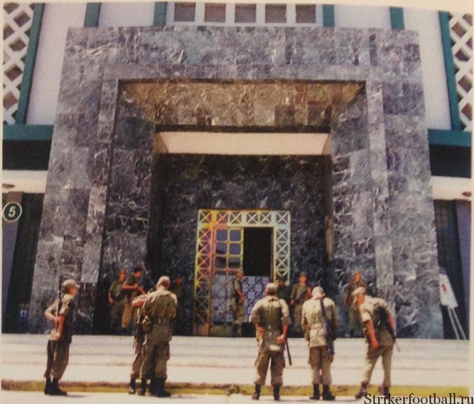 Несколько солдат перуанской армии стоят на страже за воротами «Национального стадиона» в Лиме, на котором произошла трагедия 1964 г.