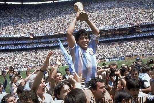 Безоговорочно лучший футболист мира Диего Марадона держит над головой Кубок Жюля Римэ на восхищенном стадионе «Ацтека* в Мехико.